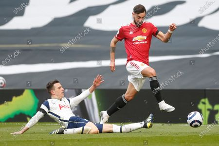 Manchester United's Bruno Fernandes is tackled by Tottenham's Giovani Lo Celso during the English Premier League soccer match between Tottenham Hotspur and Manchester United at the Tottenham Hotspur Stadium in London