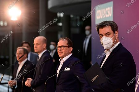 From left, the chairman of the German Christian Democratic Party (CDU), Armin Laschet, parliamentary group leader of the conservative CDU/CSU union, Ralph Brinkhaus, Christian Social Union (CSU) parliamentary group leader Alexander Dobrindt and the chairman of the German Christian Social Union (CSU) Markus Soeder after a statement following a closed meeting of the federal parliament factions of both parties in Berlin, Germany, . The two party chairmen and German state governors want to become the center-right candidate for the country's Sept. 26 national election, the German news agency dpa reported Sunday