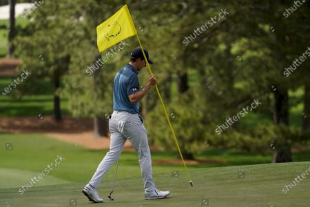 Jordan Spieth carries the flag back to the hole on the seventh green during the final round of the Masters golf tournament, in Augusta, Ga