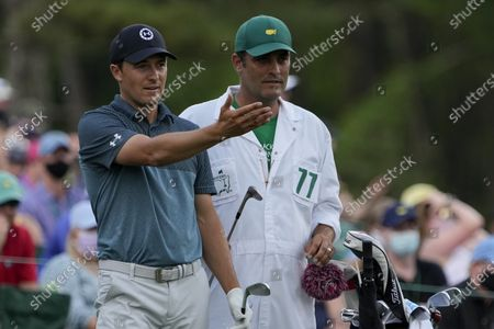 Jordan Spieth discusses his tee shot with his caddie Michael Greller on the 12th hole during the final round of the Masters golf tournament, in Augusta, Ga