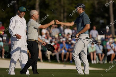 Jordan Spieth, right, fist bumps with Brian Harman on the 18th green during the final round of the Masters golf tournament, in Augusta, Ga