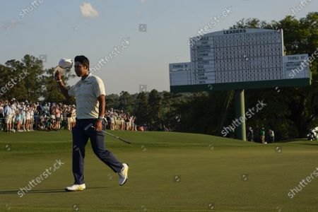 Hideki Matsuyama, of Japan, waves his cap after winning the Masters golf tournament, in Augusta, Ga