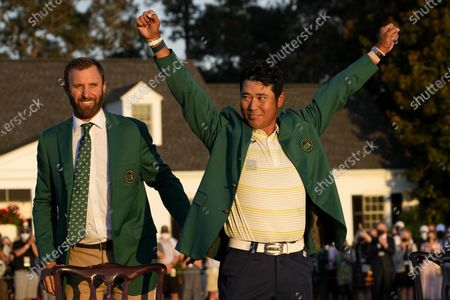 Hideki Matsuyama, of Japan, puts on the champion's green jacket after winning the Masters golf tournament as Dustin Johnson watches, in Augusta, Ga