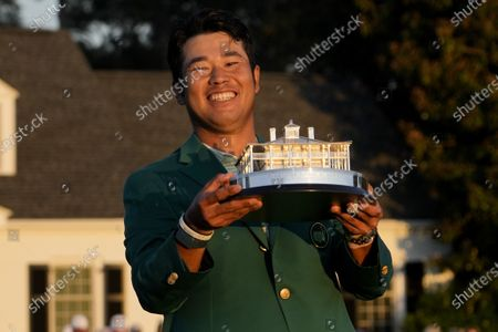 Hideki Matsuyama, of Japan, holds the trophy after winning the Masters golf tournament, in Augusta, Ga