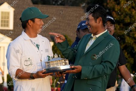 Hideki Matsuyama, of Japan, holds his trophy with his caddie Shota Hayafuji after winning the Masters golf tournament, in Augusta, Ga