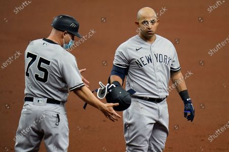 Stock Picture of New York Yankees' Rougned Odor, right, hands his helmet to first base coach Reggie Willits after popping out against the Tampa Bay Rays during the second inning of a baseball game, in St. Petersburg, Fla