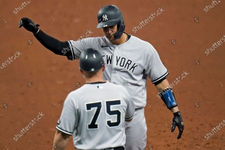 New York Yankees' Gary Sanchez (24) celebrates with first base coach Reggie Willits after his RBI single off Tampa Bay Rays relief pitcher Collin McHugh during the 10th inning of a baseball game, in St. Petersburg, Fla
