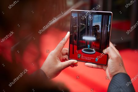 Stock Photo of Sunday 11th April 2021, London: Clara Amfo at Royal Albert Hall using Samsung Galaxy Z Fold2 5G, was one of thousands who got a first-look of Liam Payne's 2021 EE BAFTA Film Awards opening performance. The mobile exclusive AR pre-show experience, created using EE's award-winning 5G network, was enjoyed by fans at home and on-the-go. Playback and the chance to get 'papped' with AR Payne is now available. More details at ee.co.uk/bafta