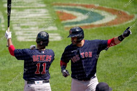 Boston Red Sox's J.D. Martinez, right, celebrates his solo home run against Baltimore Orioles pitcher Mac Sceroler with Rafael Devers (11) during the sixth inning of a baseball game, in Baltimore