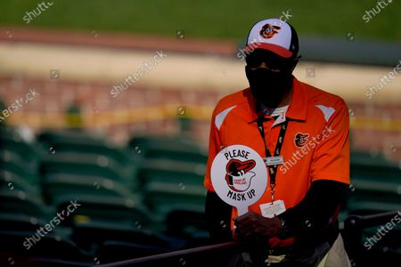 An usher holds a sign encouraging fans to wear a face mask to protect against COVID-19 during the seventh inning of a baseball game between the Baltimore Orioles and the Boston Red Sox, in Baltimore