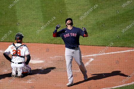 Boston Red Sox's J.D. Martinez reacts after hitting a solo home run off Baltimore Orioles starting pitcher Tyler Wells during the eighth inning of a baseball game, in Baltimore