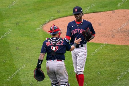 Boston Red Sox relief pitcher Phillips Valdez, top, and catcher Christian Vazquez react after a baseball game against the Baltimore Orioles, in Baltimore. The Red Sox won 14-9