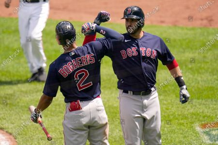 Boston Red Sox's J.D. Martinez, right, is greeted near home plate by Xander Bogaerts after hitting a solo home run off Baltimore Orioles starting pitcher Jorge Lopez during the third inning of a baseball game, in Baltimore
