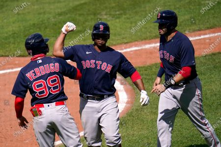 Boston Red Sox's Rafael Devers, center, celebrates his three-run home run with Alex Verdugo, left, and J.D. Martinez after he drove them home on a pitch by Baltimore Orioles pitcher Mac Sceroler during the fifth inning of a baseball game, in Baltimore