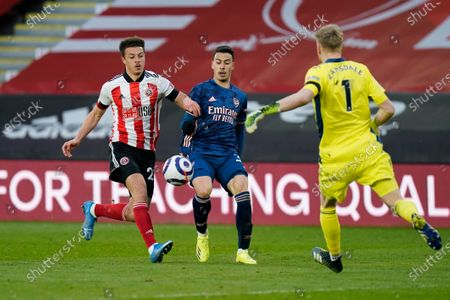 Sheffield United's Ethan Ampadu, left, and Arsenal's Gabriel Martinelli, center, fight for the ball during an English Premier League soccer match between Sheffield United and Arsenal at the Bramall Lane stadium in Sheffield, England