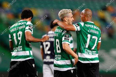 Sporting's Pedro Goncalves (C) celebrates with his teammates Joao Mario (R) and Tiagio Tomas (L) after scoring a goal against Famalicao during the Portuguese First League soccer match at Alvalade Stadium in Lisbon, Portugal, 11 April 2021.