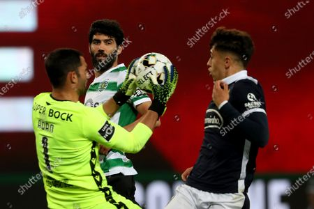 Luis Neto of Sporting CP (C ) looks on as Sporting's goalkeeper Antonio Adan makes a safe during the Portuguese League football match between Sporting CP and FC Famalicao at Jose Alvalade stadium in Lisbon, Portugal on April 11, 2021.