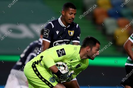 Sporting's goalkeeper Antonio Adan vies with Anderson Oliveira of FC Famalicao during the Portuguese League football match between Sporting CP and FC Famalicao at Jose Alvalade stadium in Lisbon, Portugal on April 11, 2021.