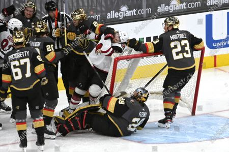 Vegas Golden Knights defenseman Alec Martinez (23) holds Arizona Coyotes left wing Michael Bunting (58) during a scuffle with defenseman Shea Theodore (27) after play stopped during the second period of an NHL hockey game, in Las Vegas