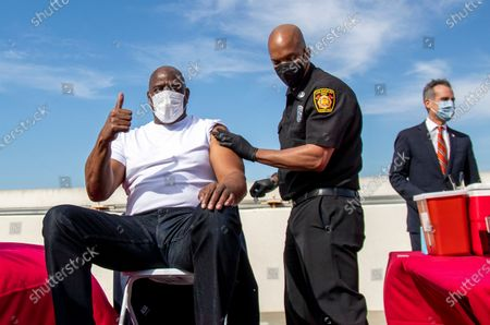 Former Los Angeles Lakers NBA basketball star Magic Johnson gives a thumbs-up after getting a vaccine from Los Angeles Fire Department Capt. Kairi Brown on the rooftop of the parking structure at the University of Southern California, as a part of a vaccination awareness event at USC, in Los Angeles. Los Angeles Mayor Eric Garcetti is in the background. The city of Los Angeles has opened up vaccines to younger people, days ahead of the state broadening eligibility to everyone 16 and up