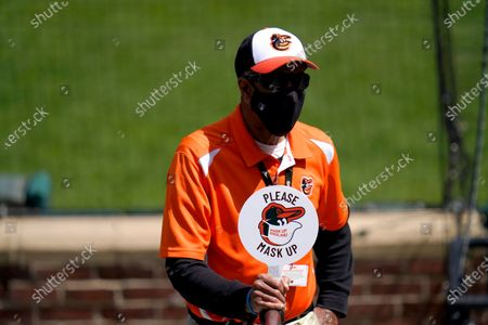 An usher holds a sign encouraging fans to wear a face mask to protect against COVID-19 during the first inning of a baseball game between the Baltimore Orioles and the Boston Red Sox, in Baltimore