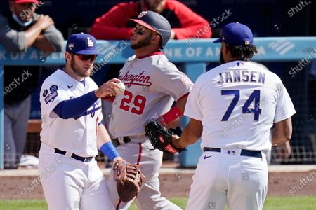 Los Angeles Dodgers' Max Muncy, left hands the ball to relief pitcher Kenley Jansen, right, after forcing out Washington Nationals' Yadiel Hernandez, center, at first to end the baseball game, in Los Angeles