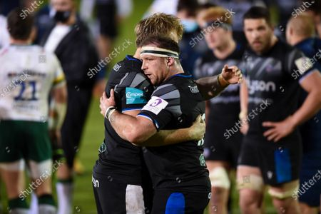 Henry Thomas of Bath Rugby hugs team-mate Josh McNally after the match
