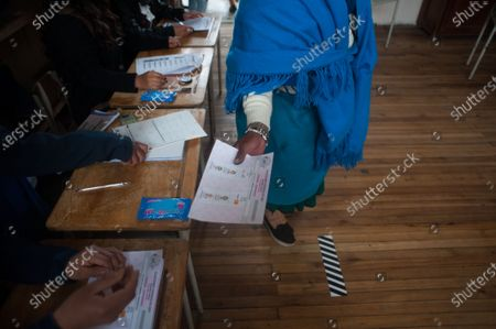 An indigenous woman receives her voting ballot after signing the voters lists. In the Cancaghua indigenous parish near Cayambe in the province of Pichincha, people from different communities move to jose antonio Vallejo educational unit to exercise their rights. This Sunday the new ruler of Ecuador is elected.