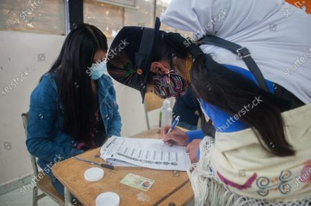 An indigenous woman receives her ballot after signing the voters lists. In the Cancaghua indigenous parish near Cayambe in the province of Pichincha, people from different communities move to jose antonio Vallejo educational unit to exercise their rights. This Sunday the new ruler of Ecuador is elected.