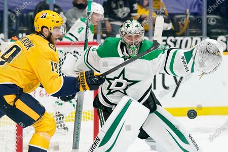 Nashville Predators center Calle Jarnkrok (19) swats at the puck as Dallas Stars goaltender Anton Khudobin (35) drops it from his glove in overtime of an NHL hockey game, in Nashville, Tenn. The Predators won 3-2 in a shoot-out