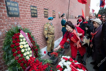 People queue to lay flowers at the grave in the Kremlin wall, left, of Yuri Gagarin, the first person who flew to space, in Moscow, Russia, . Russia on Monday marks the 60th anniversary of Gagarin's pioneering mission on April 12 1961, the first human flight to orbit that opened the space era