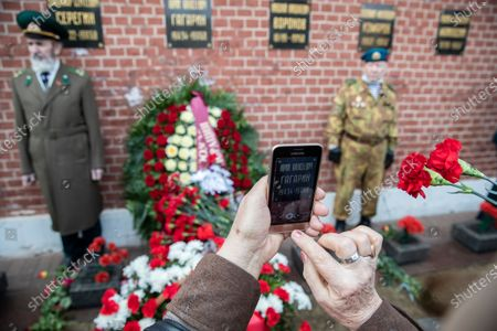 """A woman takes a picture with her smartphone of the grave of Yuri Gagarin, the first person who flew to space, in the Kremlin wall, as people come to lay flowers in Moscow, Russia, . Russia on Monday marks the 60th anniversary of Gagarin's pioneering mission on April 12 1961, the first human flight to orbit that opened the space era. The sign on the smartphone screen reads """"Yuri Alekseevich Gagarin 1934 - 1968"""