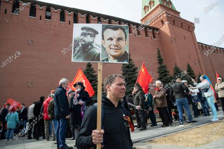 Man holds portraits of Soviet leader Josef Stalin, left, and Yuri Gagarin as people queue to lay flowers at the grave of Yuri Gagarin, the first person who flew to space, in the Kremlin wall in Moscow, Russia, . Russia on Monday marks the 60th anniversary of Gagarin's pioneering mission on April 12 1961, the first human flight to orbit that opened the space era