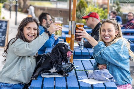 Stock Photo of Thirsty work. Pub goers (left) Gabriella Lucena 24 and Gabrielle West 28 with 1 year old Lola a Cocker Spaniel enjoy a pint and a soft drink along the Thames at Hammersmith, West London for the fist time in months as pubs and shops across England welcome back customers after Covid-19 restrictions were lifted today. Prime Minister Boris Johnson announced last week that non-essential shop, restaurants with outside seating , hairdressers and gyms can reopen today after 4 months of Covid-19 lockdowns.