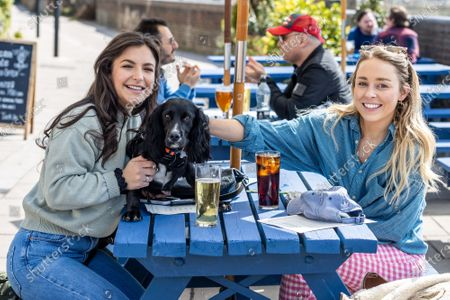 Pub goers (left) Gabriella Lucena 24 and Gabrielle West 28 with 1 year old Lola a Cocker Spaniel enjoy a pint and a soft drink along the Thames at Hammersmith, West London for the fist time in months as pubs and shops across England welcome back customers after Covid-19 restrictions were lifted today. Prime Minister Boris Johnson announced last week that non-essential shop, restaurants with outside seating , hairdressers and gyms can reopen today after 4 months of Covid-19 lockdowns.