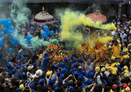 Nepalese devotees of the Newar community, an ancient community of Kathmandu, wearing red, blue and yellow caps celebrate the chariot festival, locally known as a 'Daya Lyagu' at Aason in Kathmandu, Nepal, 12 April 2021. The festival marks victory of Goddess Durga over a demon who used to kill and devour local children in ancient days.