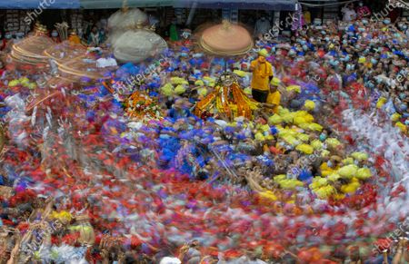 Stock Photo of A picture taken with slow shutter speed shows Nepalese devotees of the Newar community, an ancient community of Kathmandu, wearing Red, Blue and Yellow caps as they parade to celebrate the chariot festival, locally known as a 'Daya Lyagu' at Aason in Kathmandu, Nepal, 12 April 2021. The festival marks the victory of the Goddess Durga over a demon who - according to the legend - used to kill and devour local children in ancient days.