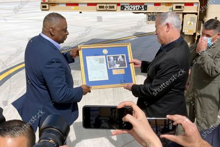 Defense Secretary Lloyd Austin, left, presents Israeli Defense Minister Benny Gantz, right, with a framed copy of a formerly Top Secret memo regarding U.S. consideration of granting official recognition of the state of Israel shortly after its creation in 1948, at Nevatim Israeli Air Force Base, in Israel. The inset photo on right shows President Truman and Secretary of State George Marshall