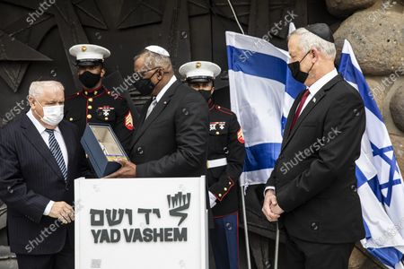 Secretary of Defense, General Lloyd James Austin III, center left, with Israeli Defense Minister Benny Gantz, right, as he receives a gift from Ronen Plot, the acting chairman of Yad Vashem, following a memorial ceremony at Yad Vashem, in Jerusalem