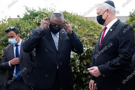 Secretary of Defense, General Lloyd James Austin III, center, removes his protective face mask as he stands with Israeli Defense Minister Benny Gantz, right, at the end of his visit to Yad Vashem, in Jerusalem