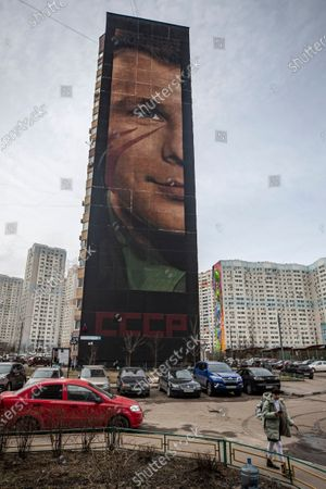 A girl walks in front the 60 meters high effigy of first USSR cosmonaut Yuri Gagarin created by graffiti artist from Italy IJorit Agoch in Odintsovo, Moscow region, Russia, 12 April 2021. The picture is painted on a nineteen-storey building in a residential area of the city of Odintsovo. Russia marks the 60th anniversary of the first human spaceflight on April 12.