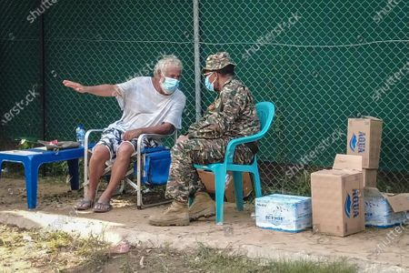 Timorese historical leader Xanana Gusmao (L) remains adamant and is still sitting under a green awning outside the center, located on Rumbia crossing, refusing to leave the site, in solidarity with the family of the deceased, in Dili, East Timor, 12 April 2021.