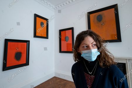 """Stock Photo of A staff member poses at the opening of Swiss artist Not Vital's """"Paintings"""" exhibition at Thaddaeus Ropac's Ely House gallery in Mayfair. These works include portraits painted on to monk's robes from Laos. The UK government's coronavirus roadmap out of lockdown has allowed art galleries to reopen today. The exhibition runs 13 April to 26 May 2021."""