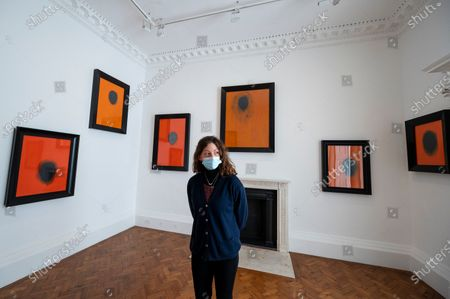 """A staff member poses at the opening of Swiss artist Not Vital's """"Paintings"""" exhibition at Thaddaeus Ropac's Ely House gallery in Mayfair. These works include portraits painted on to monk's robes from Laos. The UK government's coronavirus roadmap out of lockdown has allowed art galleries to reopen today. The exhibition runs 13 April to 26 May 2021."""