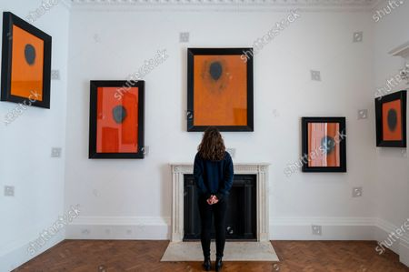 """Stock Image of A staff member poses at the opening of Swiss artist Not Vital's """"Paintings"""" exhibition at Thaddaeus Ropac's Ely House gallery in Mayfair. These works include portraits painted on to monk's robes from Laos. The UK government's coronavirus roadmap out of lockdown has allowed art galleries to reopen today. The exhibition runs 13 April to 26 May 2021."""