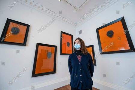 """Stock Picture of A staff member poses at the opening of Swiss artist Not Vital's """"Paintings"""" exhibition at Thaddaeus Ropac's Ely House gallery in Mayfair. These works include portraits painted on to monk's robes from Laos. The UK government's coronavirus roadmap out of lockdown has allowed art galleries to reopen today. The exhibition runs 13 April to 26 May 2021."""