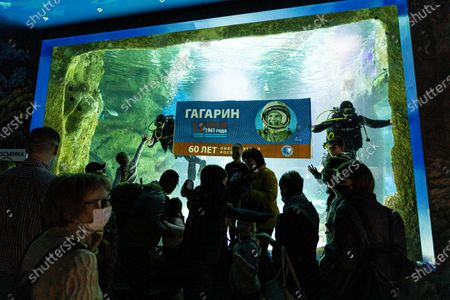 Divers unfold a banner marking the 60th anniversary of the first human flight to space by Yuri Gagarin at an aquarium at VDNKh (The Exhibition of Achievements of National Economy) in Moscow, Russia, . Gagarin's flight on April 12 1961 and has been celebrated ever since as a major national triumph