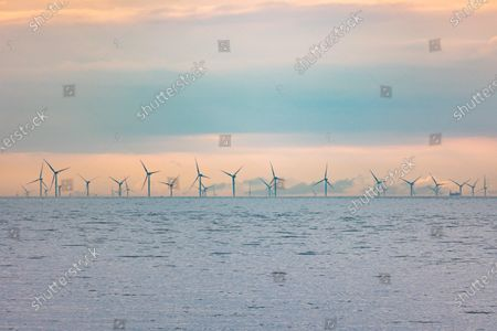 Off-shore wind park of windmills generating green renewable electric energy 20 kilometers away from the Dutch coast between the Netherlands and the United Kingdom during dusk sunset time, with clouds and ships over the horizon of the sea. The wind turbine generators  create sustainable green energy from the wind power, jet stream of air in the atmosphere, the park installed in the North Sea as seen from Oosterschelde in Zeeland in the Netherlands on April 10, 2021