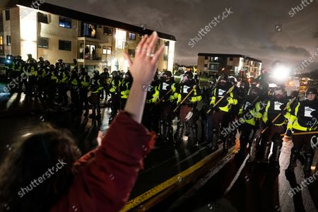 Demonstrator raises their hand while facing off against a perimeter of police as they defy an order to disperse during a protest against the police shooting of Daunte Wright, late, in Brooklyn Center, Minn