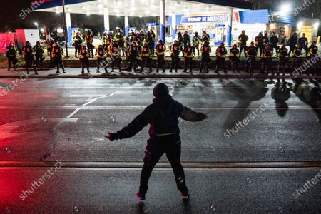 Stock Image of Demonstrator heckles authorities who advanced into a gas station after issuing orders for crowds to disperse during a protest against the police shooting of Daunte Wright, late, in Brooklyn Center, Minn